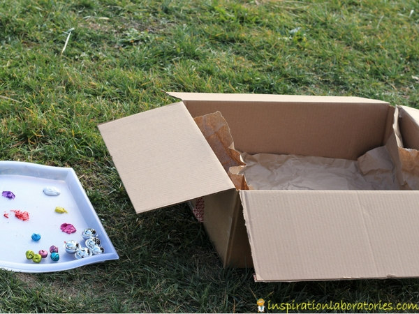 Set up a jingle bell drop painting activity outside in a box.