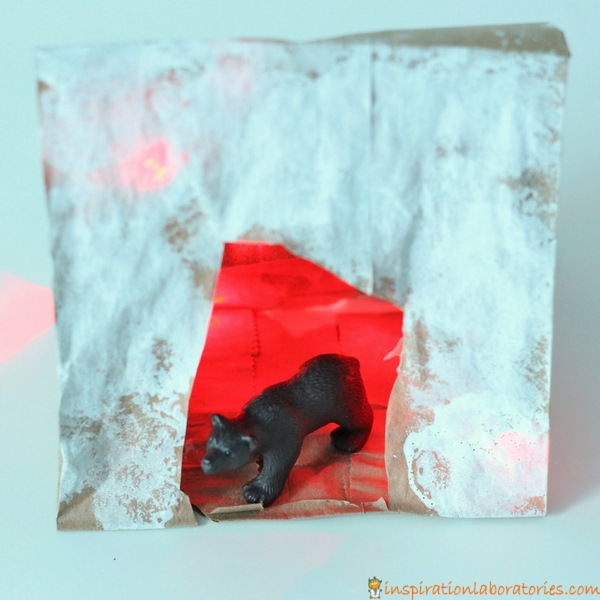 Add lights to a paper bag bear cave craft.