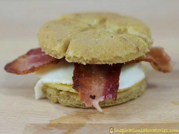 Make a delicious cinnamon roll breakfast sandwich with bacon, egg, and cheese.