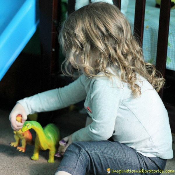 girl playing with two dinosaur toys