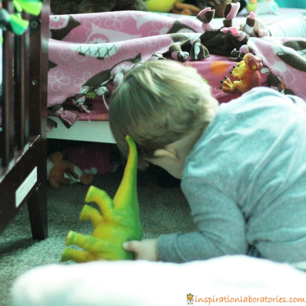 toddler looking under bed for dinosaur toy