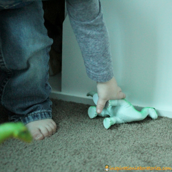 toddler picking up toy dinosaur from floor