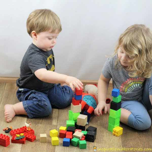 preschoolers stacking blocks with a toy fox