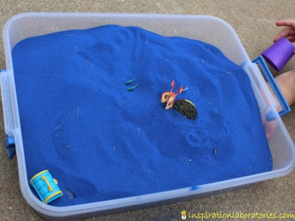 Sensory bins are great for pretend play. Blue colored sand with toy dragons shown.